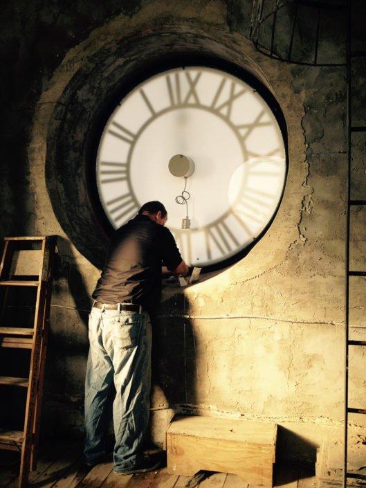 Worker servicing tower clock