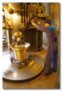 A bell foundry worker tuning a bell.