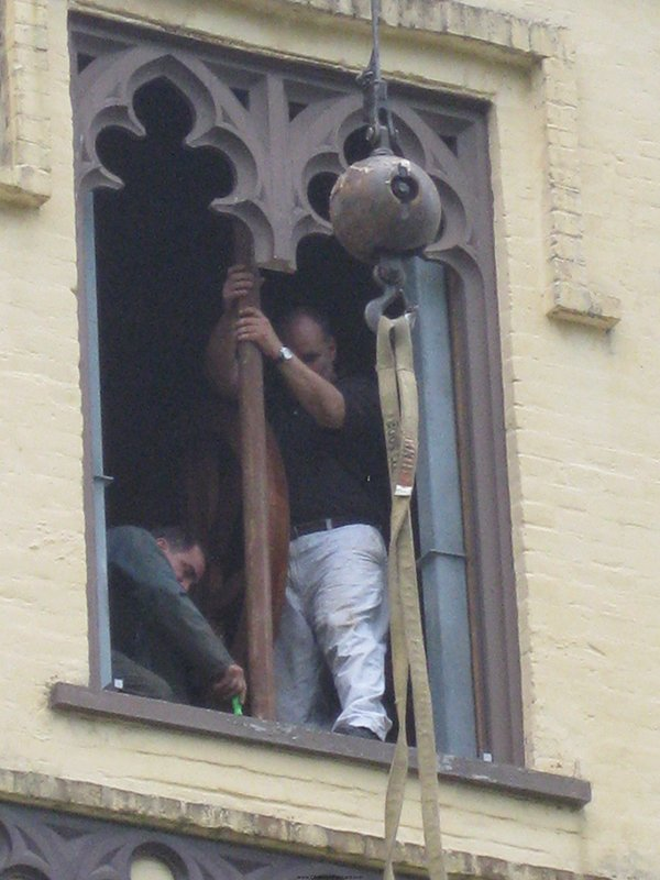 Workers install new cast bronze bell in the Chapel of the Cross